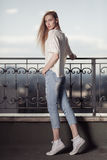 Fashion model. Summer look. Jeans, sneakers, sweater. On city background Royalty Free Stock Image
