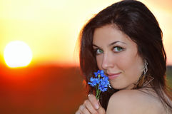 Fashion model on sunset. With bunch of  blue flowers Stock Photo