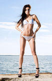 Fashion model in a swimsuit. Woman posing on a pier. Royalty Free Stock Photography