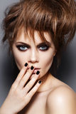 Fashion model with tousled hair, make-up, manicure. Portrait of young fashion woman model with tousled punk rock hairstyle, dark make-up, black nail polish Stock Photos