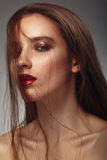 Fashion model with tousled hair, makeup. Royalty Free Stock Photography