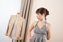Fashion model trying gray dress in designer studio Stock Images
