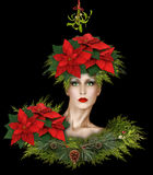 Fashion Christmas Fantasy With Mistletoe and Poinsettias. Fashion model under the mistletoe wearing poinsettias and pine cones with winter berries stock images