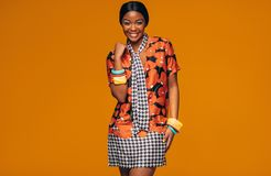 Fashion model with vivid make up in studio. African young woman with vivid make up in studio. Portrait of fashion model standing against orange background Royalty Free Stock Images