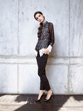 Fashion model wearing black lace shirt and trousers posing in studio. On concrete wall Royalty Free Stock Photos