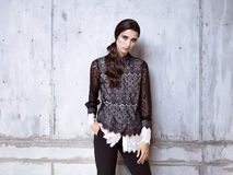 Fashion model wearing black lace shirt and trousers posing in studio. On concrete wall Stock Images