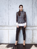 Fashion model wearing black lace shirt and trousers posing in studio. On concrete wall Stock Photography
