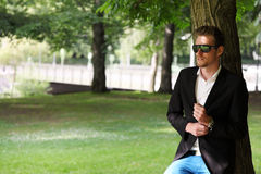 Fashion model wearing a blazer and jeans. Attractive man in blue jeans and black blazer in a park, leaning against a tree on a sunny summer day Stock Photo