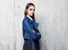 Fashion model wearing denim jacket and long black skirt posing in studio Stock Photos
