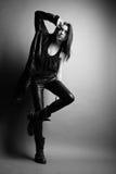 Fashion model wearing leather pants and jacket. Posing on grey background Stock Photo