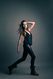 Fashion model wearing leather pants posing on grey Royalty Free Stock Photos