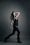 Fashion model wearing leather pants posing on grey Royalty Free Stock Image