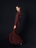 Fashion model wearing long maroon dress on black background Royalty Free Stock Image