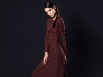 Fashion model wearing long maroon dress on black background Stock Images