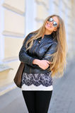 Fashion model in sunglasses with bag smiling outdoors Royalty Free Stock Photo