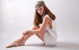 Fashion Model in White Dress and Olive Colored Hat. An image of a beautiful model wearing a white dress with jagged edges and a stylish olive colored hat Stock Photography