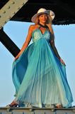 Fashion model in white hat and blue resort dress posing under the bridge Royalty Free Stock Images