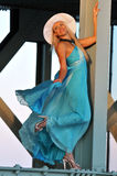 Fashion model in white hat and blue resort dress posing under the bridge Stock Images