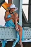 Fashion model in white hat and blue resort dress posing under the bridge Royalty Free Stock Photo
