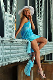 Fashion model in white hat and blue resort dress posing under the bridge Royalty Free Stock Image