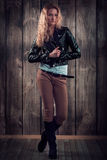 Fashion Model With Curly Hair Dressed In Black Jacket, Denim Pants And Tall Boots Over Wooden Wall Background Stock Photography