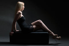 Fashion model woman in black dress sitting on a sofa Stock Image
