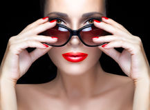 Fashion Model Woman in Black Oversized Sunglasses. Bright Makeup. Beautiful fashion model girl with hands on stylish black sunglasses looking at camera. Bright Stock Photo