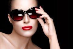 Fashion Model Woman in Black Oversized Sunglasses. Colorful Make. Beautiful fashion model girl with Hand on her stylish oversized sunglasses looking at camera Stock Photo