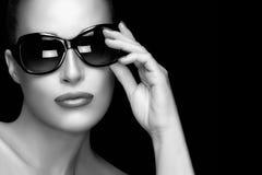 Fashion Model Woman in Black Oversized Sunglasses. Monochrome Po. Beautiful fashion model girl with Hand on her stylish oversized sunglasses looking at camera Stock Images