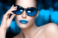 Fashion Model Woman in Blue Oversized Sunglasses. Colorful Makeup. Beautiful fashion model girl with Hand on her stylish oversized sunglasses looking at camera stock photography