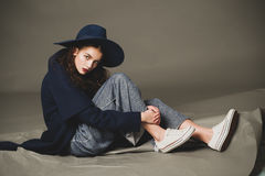 Fashion model woman coat and hat urban style pose Stock Image
