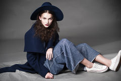 Fashion model woman coat and hat urban style pose Stock Photography