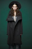 Fashion model woman coat and hat urban style pose Royalty Free Stock Photo