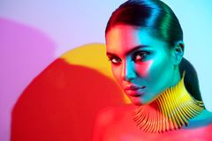 Fashion model woman in colorful bright lights. Posing. Portrait of beautiful sexy girl with trendy makeup Royalty Free Stock Image