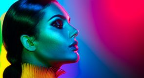 Fashion model woman in colorful bright lights posing. Portrait of girl with trendy makeup. Fashion model woman in colorful bright lights posing. Portrait of royalty free stock images