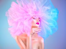 Fashion model woman in colorful bright lights posing, portrait of beautiful girl with trendy makeup and colorful pink hairdo. Art design stock image