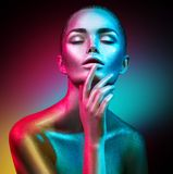 Fashion model woman in colorful bright sparkles and neon lights posing in studio, portrait of beautiful sexy girl Stock Image