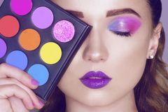 Fashion model woman creative pink and blue make up.  Beautiful Eyes Glitter . Purple bright lips, long cerly hair. Model holding royalty free stock images