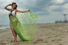 Fashion model woman in design bikini with blowing cover up posing pretty on the beach. Royalty Free Stock Images