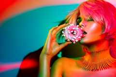 Fashion model woman with donut. Posing in studio in colorful bright lights Royalty Free Stock Images