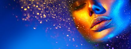 Fashion model woman face in bright sparkles, colorful neon lights, beautiful sexy girl lips. Trendy glowing gold skin