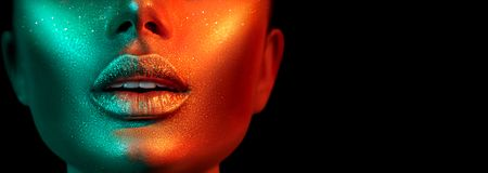 Fashion model woman face in bright sparkles, colorful neon lights, beautiful sexy girl lips. Trendy glowing gold skin make-up. Glitter metallic shine makeup royalty free stock photo