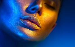 Fashion model woman face in bright sparkles, colorful neon lights, beautiful sexy girl lips. Trendy glowing gold skin makeup stock photo