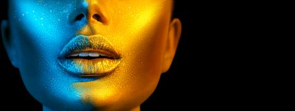 Fashion model woman face in bright sparkles, colorful neon lights, beautiful sexy girl lips. Trendy glowing gold skin makeup royalty free stock images