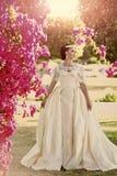 Fashion model woman fece close up. Face woman wiht happy emotion. Bride in white wedding dress posing near pink bush. Stock Photos
