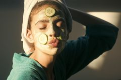 Fashion model woman fece close up. Face woman wiht happy emotion. Cosmetics, cosmetology, dermatology. Girl or woman face with cucumber mask, towel on head royalty free stock photography