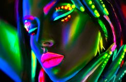 Fashion model woman in neon light. Beautiful model girl with colorful fluorescent makeup. Fashion model woman in neon light. Portrait of beautiful model girl stock photo