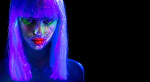 Fashion model woman in neon light. Beautiful model girl with colorful bright fluorescent makeup isolated on black. Ultraviolet. UV royalty free stock image