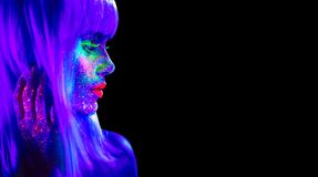Fashion model woman in neon light. Beautiful model girl with colorful bright fluorescent makeup isolated on black. Ultraviolet, UV stock image