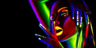 Fashion model woman in neon light. Beautiful model girl with colorful fluorescent makeup Royalty Free Stock Images